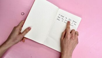 words written in a diary lying on a pink desk - personal branding london