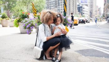 mum holding her child in New York City - mum bloggers in London